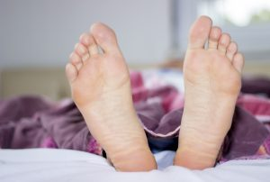 Low section of sleeping young man's feet